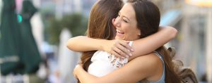 two women hugging after a successful addiction treatment
