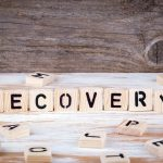 Recovery from wooden letters on wooden background