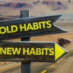 Old Habits - New Habits signpost in a desert road background