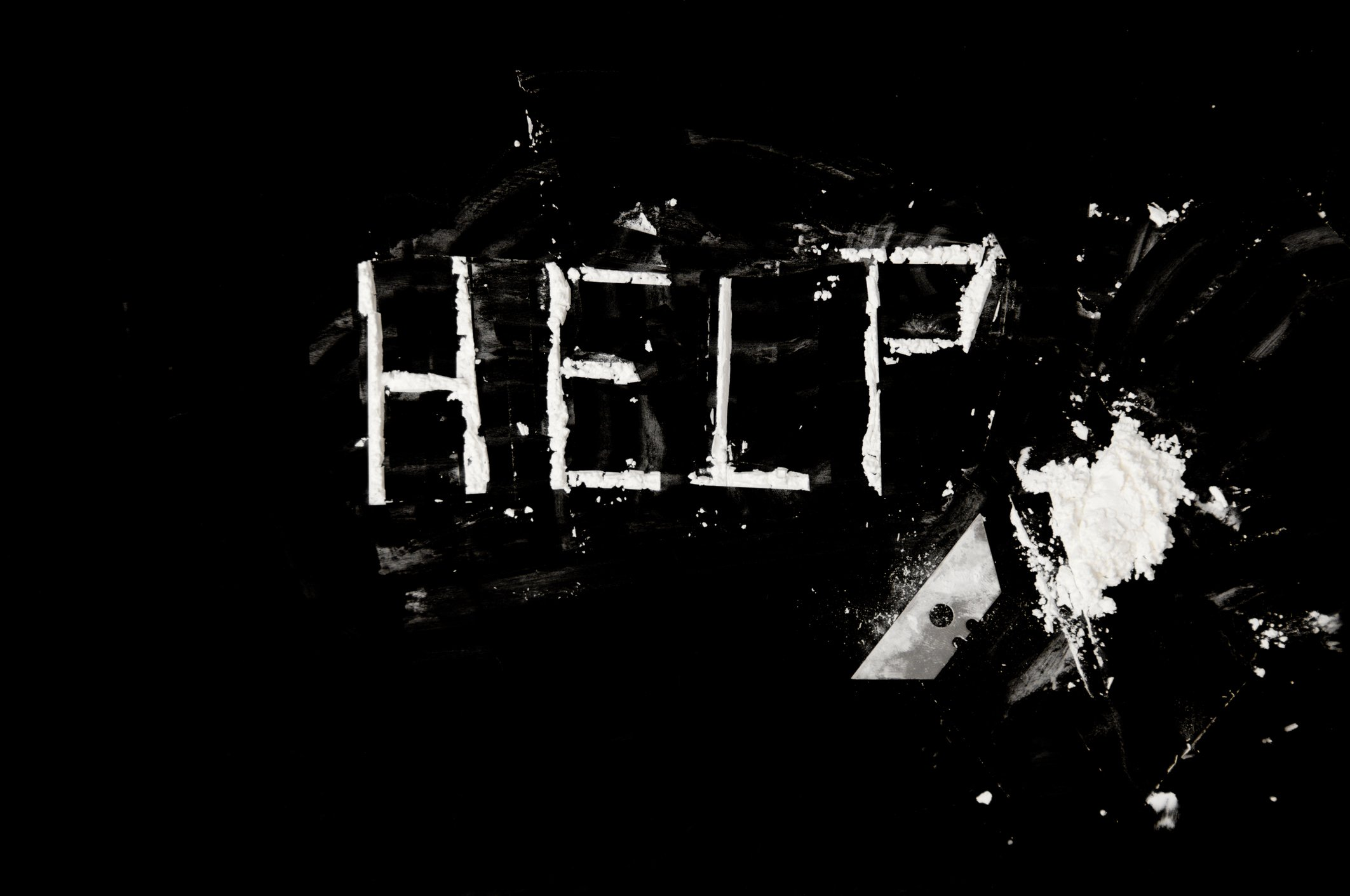 The word help written in cocaine with a razor blade.