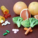 Oranges, grapefruit, pills, tablets, prescriptions on wooden surface