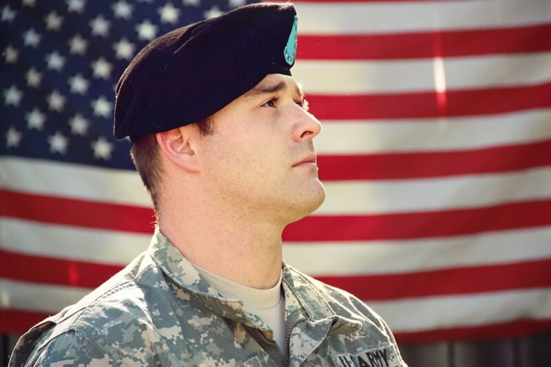 Man wearing combat hat and army uniform near US flag looks up in attention